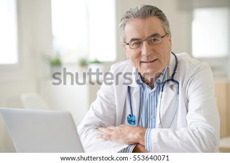 Portrait of senior doctor sitting in medical office