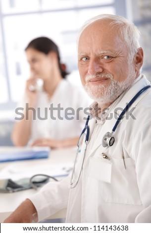 Portrait of senior doctor smiling at doctor\'s room.