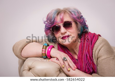 Portrait of senior elegant extravagant woman at home interior. Retired stylish person with sun glasses, bright make-up, and pink colorful hair and golden clothes.  #582654022