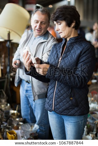 Portrait of senior family couple looking vintage goods at flea market