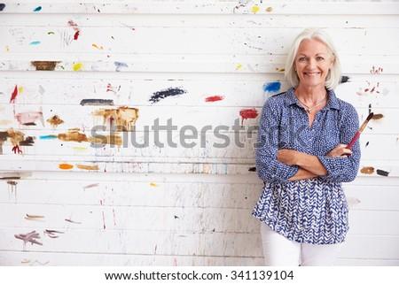 Portrait Of Senior Female Artist Against Paint Covered Wall