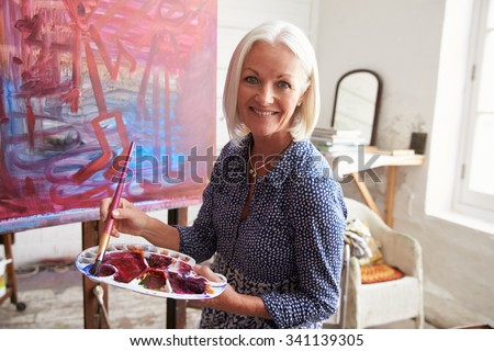 Portrait Of Senior Female Artist Working On Painting In Studio