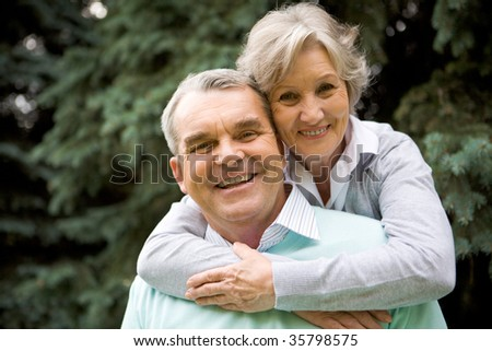 Portrait of senior female embracing her husband while he laughing and both looking at camera