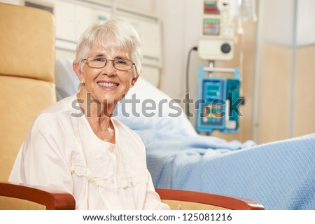 Portrait Of Senior Female Patient Seated In Chair By Hospital Bed