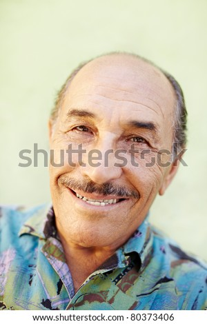 portrait of senior hispanic man looking at camera against green wall and smiling. Horizontal shape, copy space