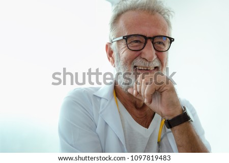 Portrait of senior laughing doctor.