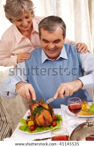 Portrait of senior man cutting roasted turkey with his happy wife behind