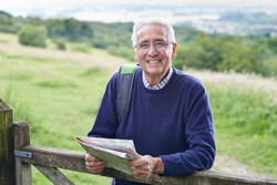 Portrait Of Senior Man Hiking In Countryside