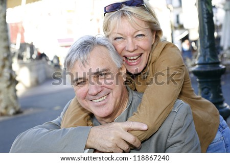 Portrait of senior man holding woman on his back