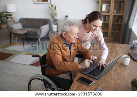 Portrait of senior man in wheelchair using laptop at retirement home with nurse assisting him, copy space