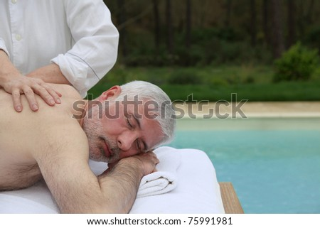 Portrait of senior man laying on a massage bed
