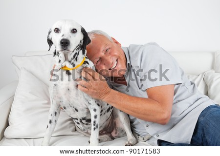 Portrait of senior man sitting on sofa with his pet dog at home