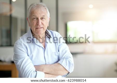 Portrait of senior man standing in living-room