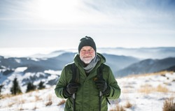 Portrait of senior man standing in snow-covered winter nature, looking at camera.