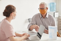 Portrait of senior man wearing masks while talking to female doctor or nurse in medical clinic, copy space