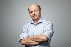 Portrait of senior man with crossed hands. He is angry