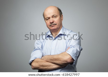 Portrait of senior man with crossed hands. He is angry #618427997