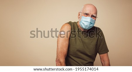 Portrait of senior man with protective face mask getting vaccine. Mature man against brown background after receiving corona virus vaccination.