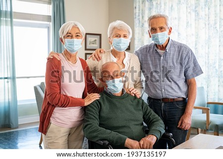 Portrait of senior men and women wearing protective face mask during the coronavirus epidemic at care facility centre. Group of seniors with disabled man wearing surgical mask while looking at camera. Foto stock ©