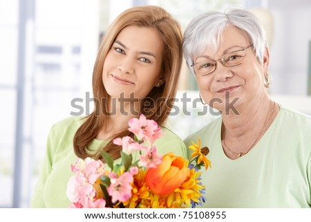 Portrait of senior mother and daughter at Mother's day, having flowers, smiling.?