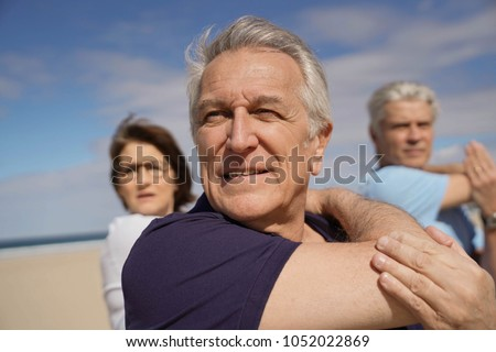 Portrait of senior people doing stretching exercises on the beach
