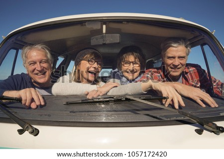 Portrait of senior people through vintage camper van windshield