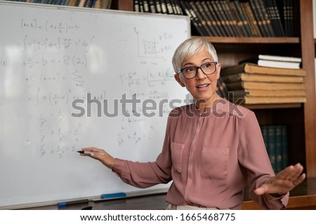 Portrait of senior professor explaining  math formulas. Mature female teacher standing in classroom and talking to her class. Lecturer explaining math formulas written on whiteboard in library.