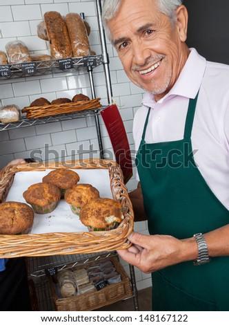 Portrait of senior salesman displaying tray of cupcakes at supermarket