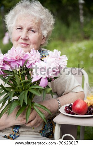 Portrait of senior smiling woman with flowers and fruit