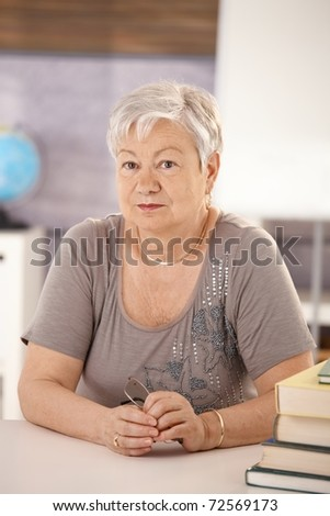 Portrait of senior teacher sitting at desk in classroom, looking at camera.?