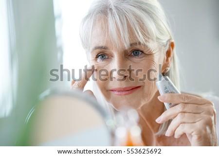 Portrait of senior woman applying anti-aging cream
