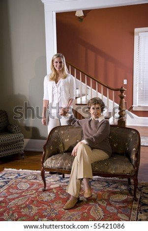 Portrait of senior woman at home on sofa with adult daughter
