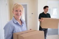 Portrait Of Senior Woman Downsizing In Retirement Carrying Boxes Into New Home On Moving Day With Removal Man Helping