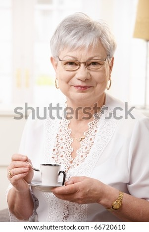 Portrait of senior woman drinking coffee at home, looking at camera smiling.?