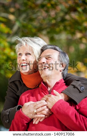Portrait of senior woman embracing her husband at the back outdoors
