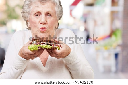 portrait of senior woman holding a delicious sandwich at street