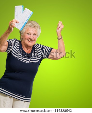 Portrait Of Senior Woman Holding Boarding Pass Cheering On Green Background