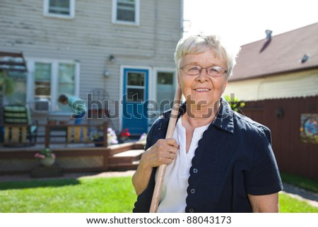 Portrait of senior woman holding gardening tool with friend in the background