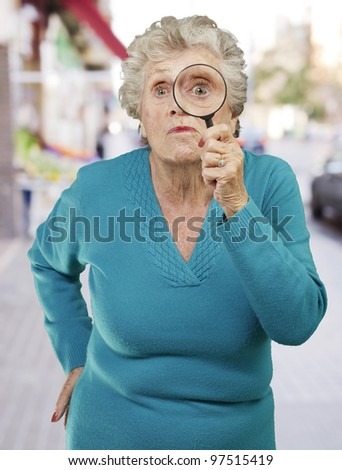 portrait of senior woman looking through a magnifying glass against a city