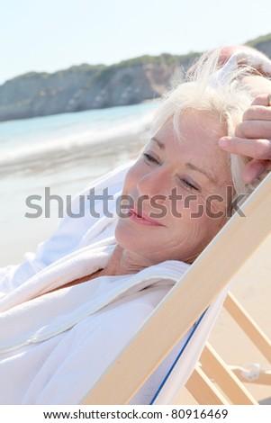 Portrait of senior woman relaxing in longchair