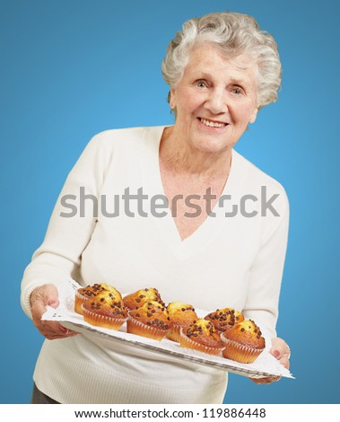 portrait of senior woman showing homemade muffins over blue