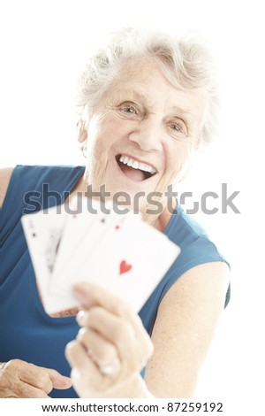portrait of senior woman showing poker cards over white