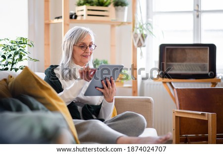 Portrait of senior woman sitting indoors on sofa at home, using tablet.