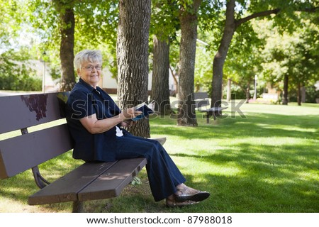 Portrait of senior woman sitting on a park bench reading a book
