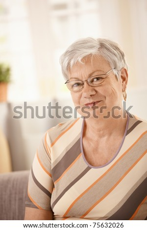 Portrait of senior woman sitting on sofa at home, looking at camera, smiling.?