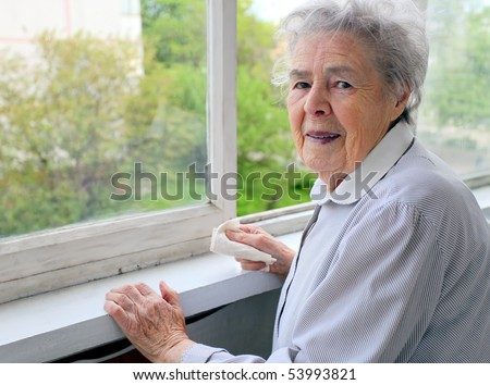 Portrait of senior woman standing at the window at her home