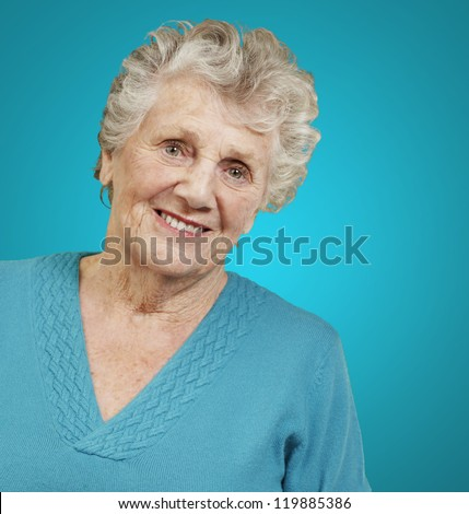 portrait of senior woman standing over blue background