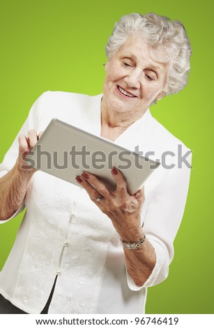 portrait of senior woman touching digital tablet over green background