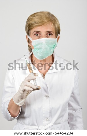 Portrait of senior woman wearing protective mask and surgical gloves and holding a syringe prepared for vaccination