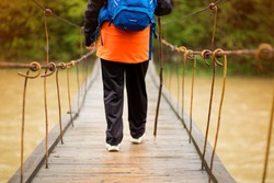 Portrait Of Senior Woman with backpack On Hike cross river in forest